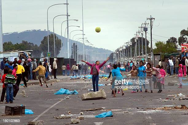 Children play with a ball amongst barricades during a protest against deficiencies in government services on August 10 in Gugulethu an impoverished...