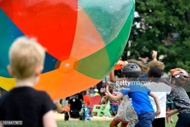 Children play with a large beach ball as residents community members and locals enjoy a popup beach in North Philadelphia when thousands of...