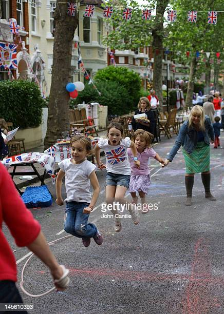 Children play with a skipping rope during a street party on Niton Street on June 2 2012 in Fulham southwest London England For only the second time...