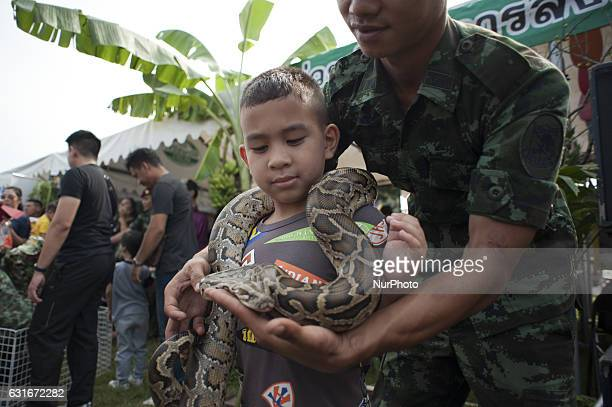 Children play with a snake during the National Children's Day event inside a military base in Bangkok Thailand on 14 January 2017