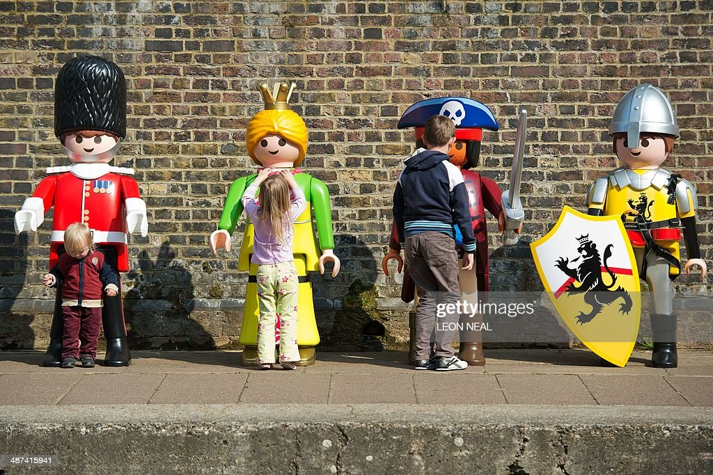 Children play with giant Playmobil figures during a photocall on the canalside at Camden in north London, on April 30, 2014, as the toy company celebrates its 40th anniversary.