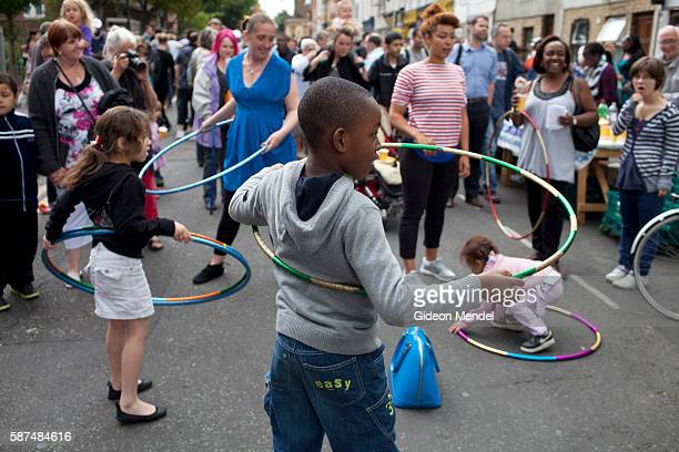 Children play with hula hoops at a community tea party held in Clarence Road in Hackney exactly a week after the violent disturbances involving a...