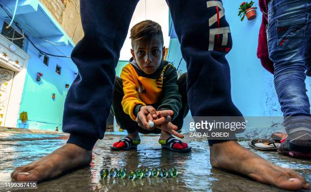 Children play with marbles together in an alley of the old town of Iraq's northern city of Mosul on February 8, 2020.