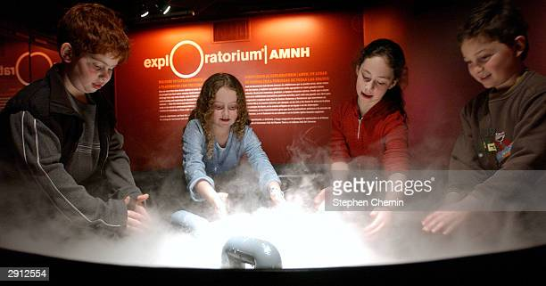 Children play with the Sea of Clouds exhibit that allows visitors to play in a large bowl of fog demonstrating turbulent air flow January 29 2004 at...