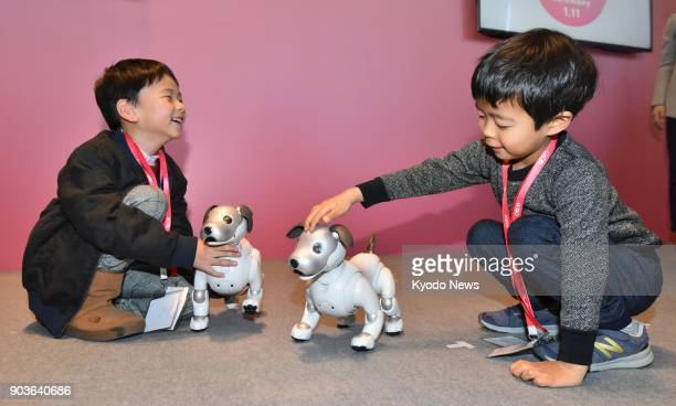 Children play with their Aibo robot dogs at the head office of Sony Corp in Tokyo on Jan 11 2018 Sony delivered the first batch of the upgraded...