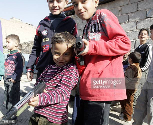 Children play with toy guns on the second day of the Eid alAdha festivities in the alKhullani neighbourood central Baghdad 20 December 2007 The Eid...
