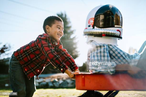 children play with wagon outside imagining space travel - toy wagon stock photos and pictures