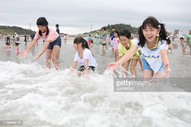 Children play with waves during the opening of the beach to members of the public at Kita Izumi in Minami Soma city, Fukushima prefecture on July 20,...