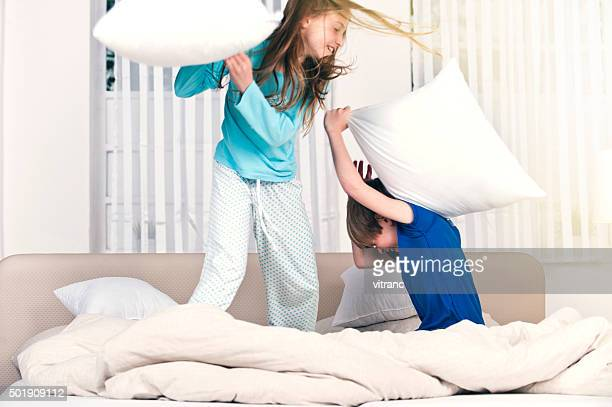 Children playfighting on parents' bed