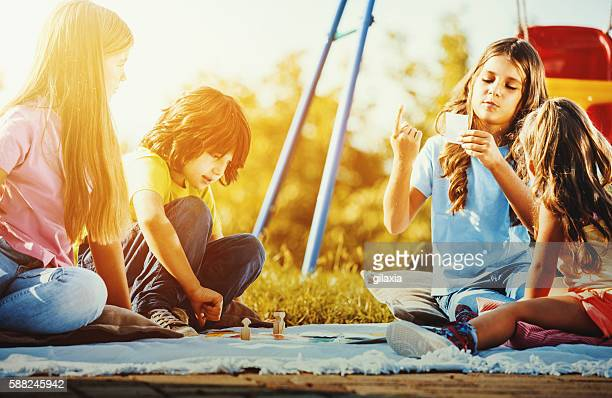Children playing a board game outdoors.