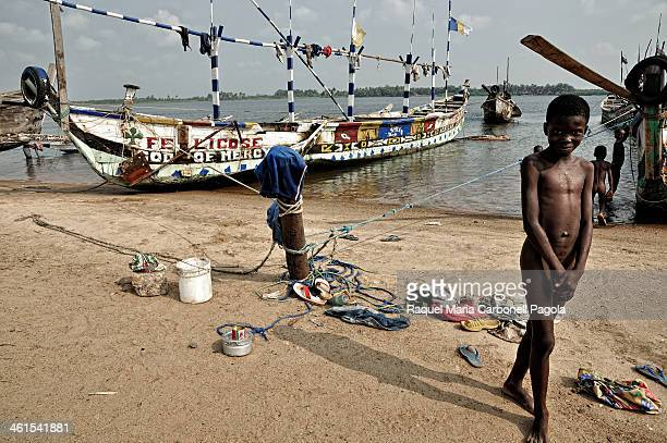 Children playing and bathing among the fishing boats in a small port