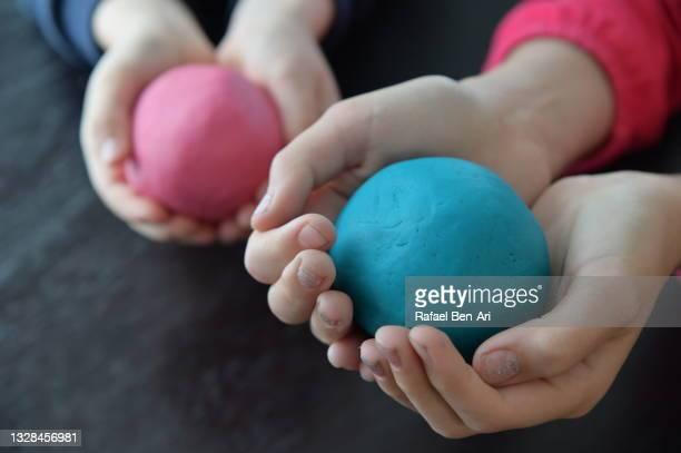 children playing and creating with colored doh - rafael ben ari imagens e fotografias de stock