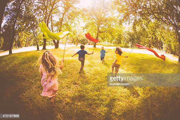 Children playing and running in a park with colourful banners