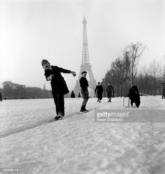 Children playing and sliding in the snow in front of the Eiffel Tower 1945 in Paris France
