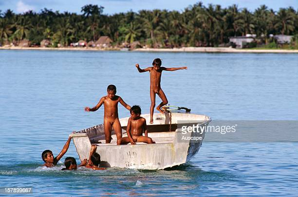 Children playing and swimming from boat Tarawa Islands Republic of Kiribati