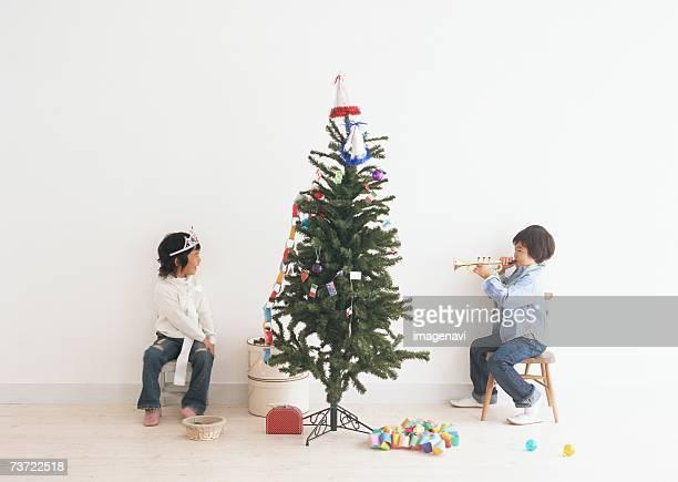 Children playing around the christmas tree
