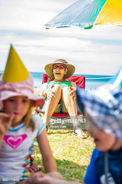 Children playing at party in front of senior woman on deck chair at coast, Waiheke Island, New Zealand