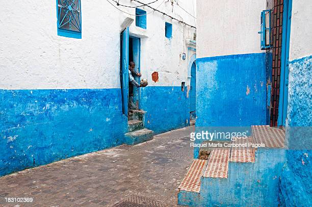 Children playing at their house doorway in Larache blue medina, Morocco, 2013
