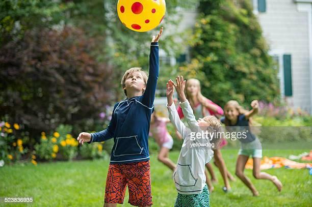 Children playing ball game in garden