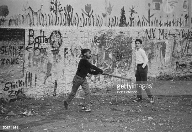 Children playing baseball in front of mural painted to brighten the slum area