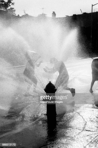 Children Playing by Water Spraying Hydrant