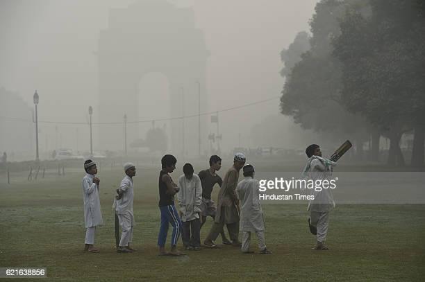 Children playing cricket near India Gate as smog engulf the city on November 7 2016 in New Delhi India A million school children were forced to stay...
