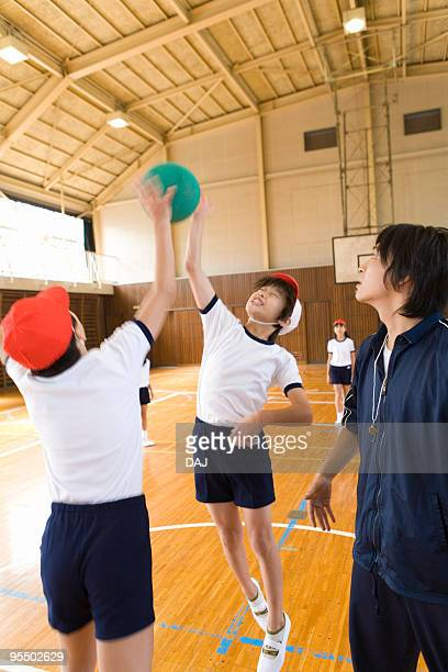 Children playing dodgeball in gym, blurred motion