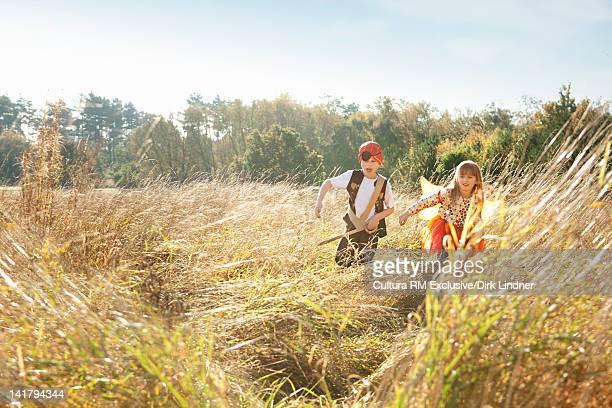 Children playing dress up in wheatfield