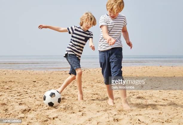 Children playing football at the beach