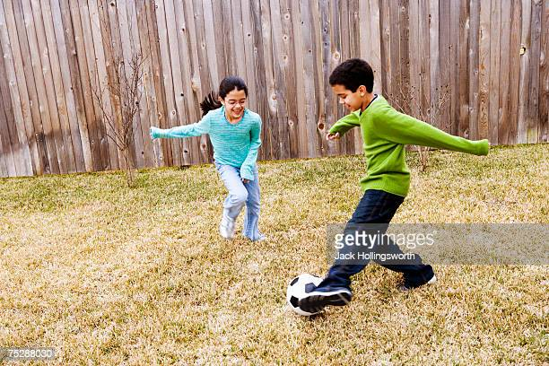 Children ( 8-11)  playing football in ground