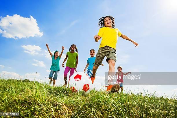 Kinder spielen Fußball auf dem Feld.