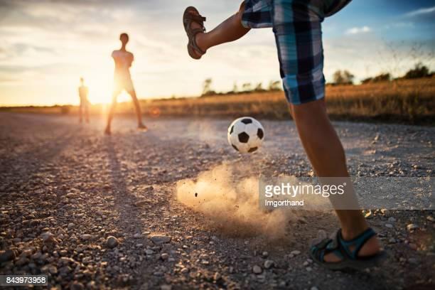 kinderen voetballen op onverharde weg - football in spain stockfoto's en -beelden