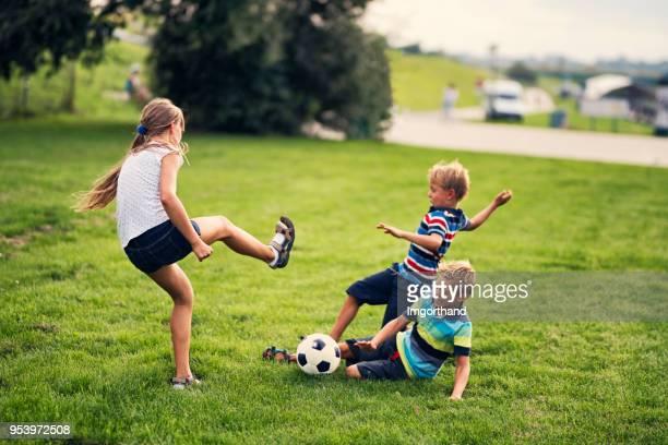 enfants jouer au football sur herbe dans le parc de la ville - tacler photos et images de collection