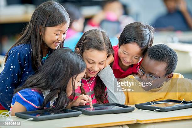 children playing games on a tablet - primary age child stock pictures, royalty-free photos & images