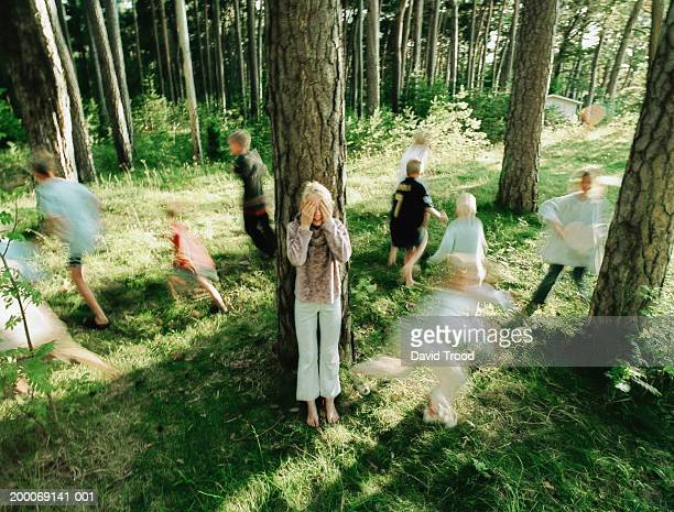 Children (6-9) playing hide and seek in forest (Blurred Motion)