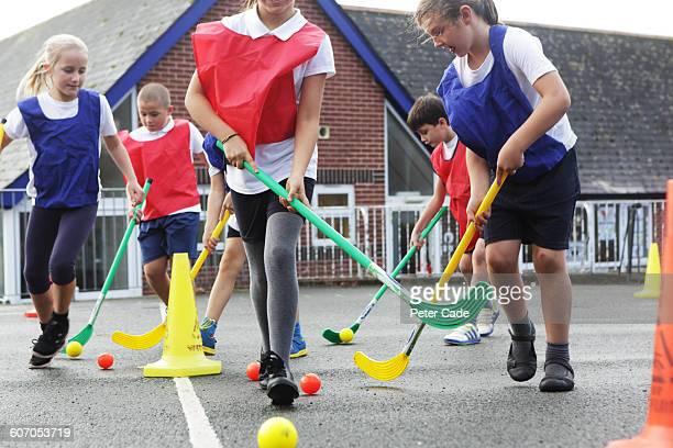 Children playing hockey in playground