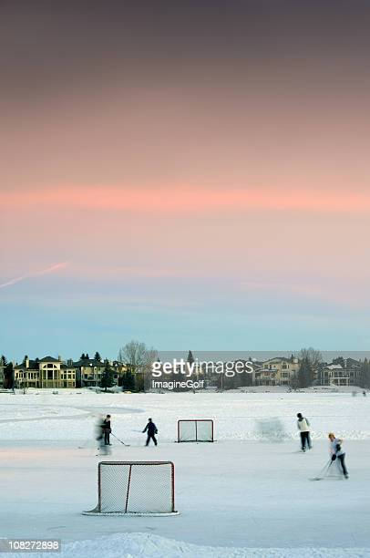 children playing hockey on pond ice - center ice hockey player stock pictures, royalty-free photos & images