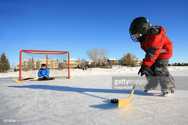 Children Playing Ice Hockey on Outdoor Pond or Rink