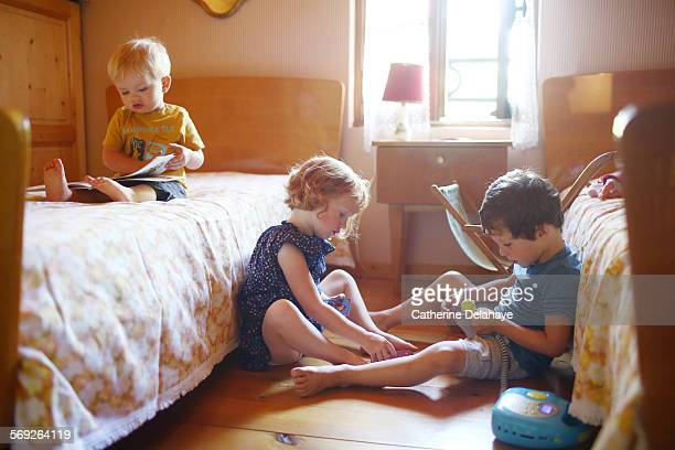 3 children playing in a bedroom
