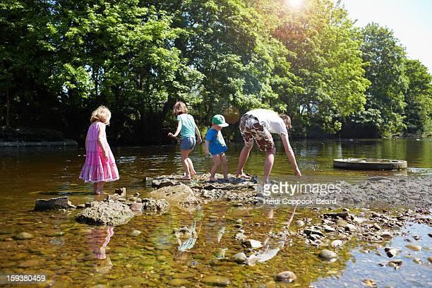 children playing in a river - heidi coppock beard stock-fotos und bilder