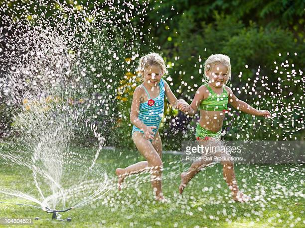 children playing in a sprinkler