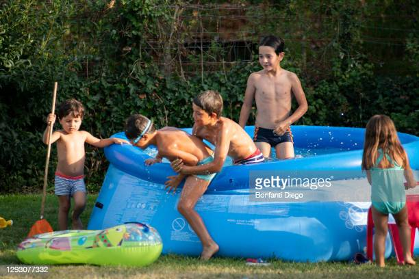 children playing in and around swimming pool - google stock pictures, royalty-free photos & images