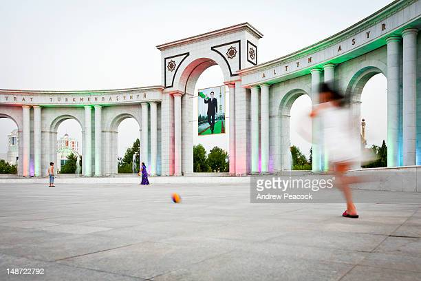 children playing in front of triumphal archway with large banner of president gurbanguly berdimuhamedow. - ashgabat stock pictures, royalty-free photos & images