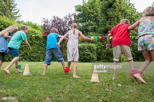 children playing in garden on a birthday party - junge gefesselt stock-fotos und bilder