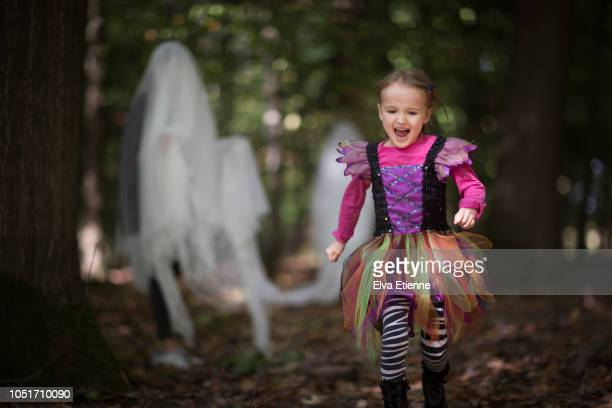 children playing in halloween costumes in a forest - ghost player foto e immagini stock
