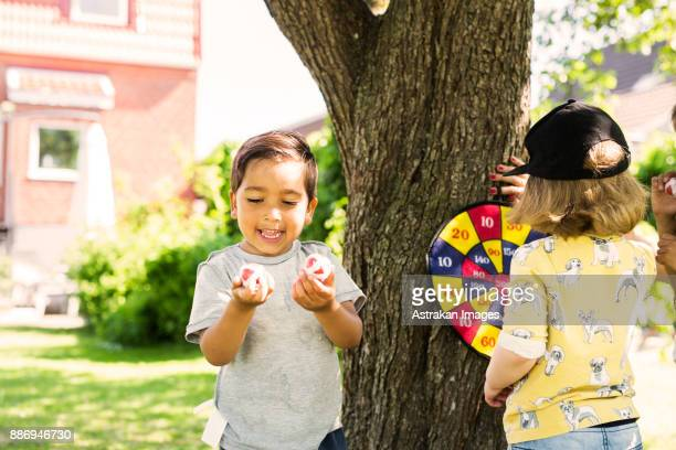 children (2-3, 6-7) playing in in front yard - darts girls stock photos and pictures
