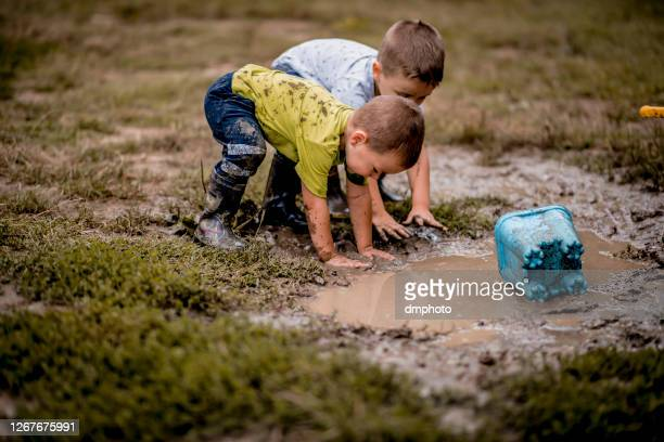 children playing in mud - mud stock pictures, royalty-free photos & images