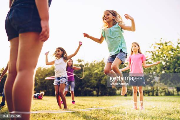 kinder spielen im park mit gummiband und reifen - skipping along stock-fotos und bilder