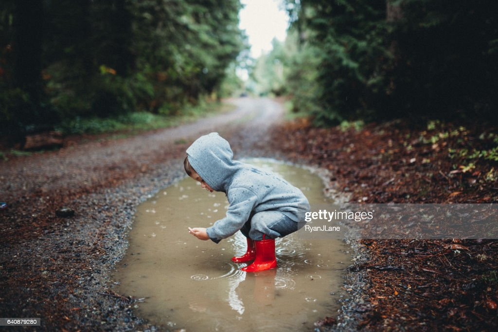 Kinder spielen im Regen Pfütze : Stock-Foto