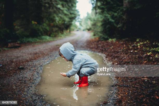 children playing in rain puddle - puddle stock pictures, royalty-free photos & images